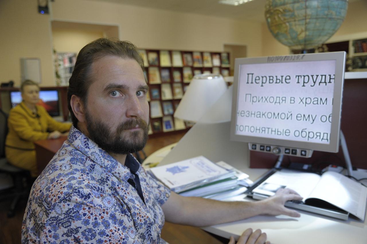 Инвалид по зрению Илья Гаврилов работает с электронной лупой, позволяющей читать книги и журналы с огромным (в сотни раз) увеличением
