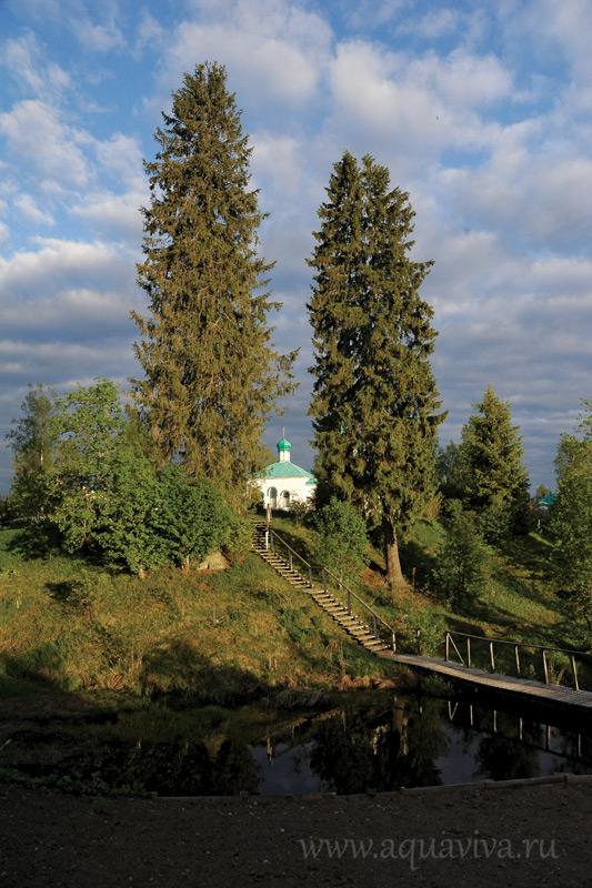 Мостик к храму. На противоположной стороне — жилой корпус и сельхозугодья