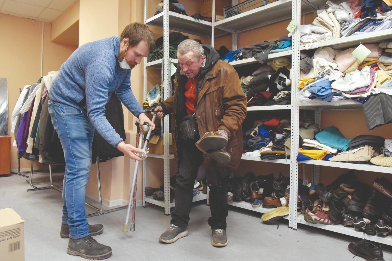 Антон помогает посетителю подобрать трость