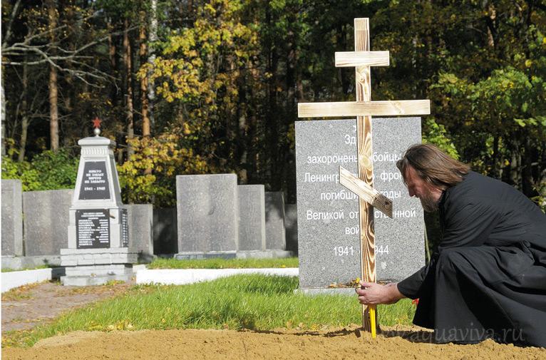 Протоиерей Валериан Жиряков зажигает свечи на месте захоронения 268 солдат и офицеров в д. Озерки